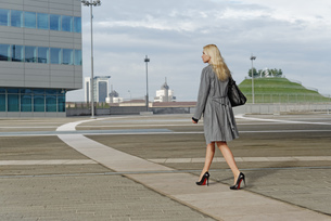 Businesswoman, walking outdoors along pathway, rear viewの写真素材 [FYI03519312]