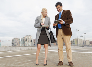 Businessman and businesswoman outdoors, holding digital tablets, sharing informationの写真素材 [FYI03519323]