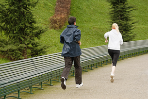 Man and woman running along pathway, rear viewの写真素材 [FYI03519325]