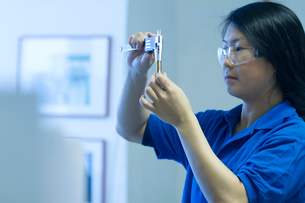 Young woman using specialist measuring deviceの写真素材 [FYI03519375]