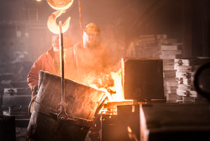 Workers pouring molten metal into moulds from flask in foundryの写真素材 [FYI03519440]