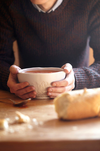 Young man at kitchen table with hands holding soup bowlの写真素材 [FYI03519462]