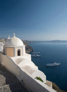 View of white washed church and sea ferries, Oia, Santorini, Cyclades, Greeceの写真素材 [FYI03519490]