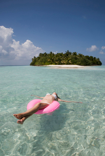 Mid adult woman floating on rubber ring in Indian Ocean, Maldivesの写真素材 [FYI03519656]