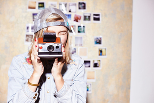 Young woman in front of photo wall taking photograph on retro cameraの写真素材 [FYI03519889]
