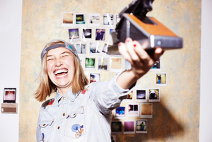 Young woman in front of photo wall taking instant selfie on retro cameraの写真素材 [FYI03519890]