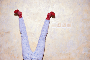 Studio shot of young womans legs upside down against wallの写真素材 [FYI03519892]
