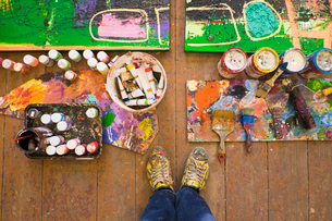 Artist selfie of feet paints and abstract painting in studioの写真素材 [FYI03519896]