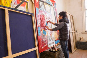Artist drawing on abstract painting in studioの写真素材 [FYI03519897]