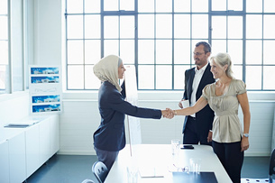 Young businesswoman shaking hands with businesswoman in officeの写真素材 [FYI03519929]