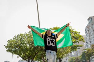Young man holding up Brazilian flag, Copacabana, Rio De Janeiro, Brazilの写真素材 [FYI03520007]