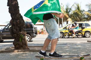Young man skateboarding wrapped in Brazilian flag, Copacabana, Rio De Janeiro, Brazilの写真素材 [FYI03520008]