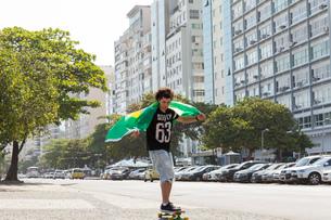 Young man skateboarding holding Brazilian flag, Copacabana, Rio De Janeiro, Brazilの写真素材 [FYI03520009]