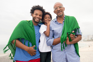 Mid adult man with father and son wrapped in Brazilian flag on Ipanema beach, Rio De Janeiro, Brazilの写真素材 [FYI03520054]