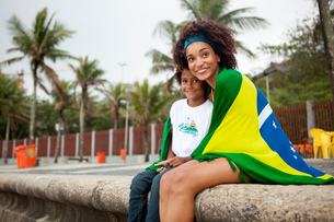 Young mother and son wrapped in Brazilian flag on Ipanema beach, Rio De Janeiro, Brazilの写真素材 [FYI03520055]