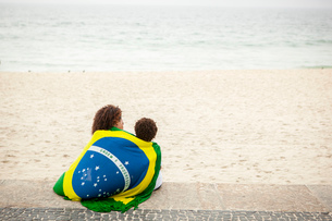 Rear view of young mother and son wrapped in Brazilian flag on Ipanema beach, Rio De Janeiro, Brazilの写真素材 [FYI03520056]