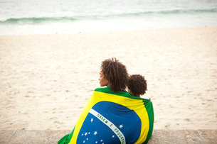 Rear view of young mother and son wrapped in Brazilian flag looking out from Ipanema beach, Rio De Jの写真素材 [FYI03520057]