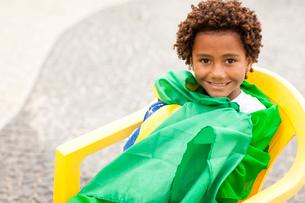 Portrait of boy wrapped up in Brazilian flag sitting on Ipanema beach, Rio De Janeiro, Brazilの写真素材 [FYI03520059]