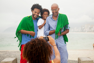 Over shoulder view of mother photographing family wrapped in Brazilian flag on Ipanema beach, Rio Deの写真素材 [FYI03520061]