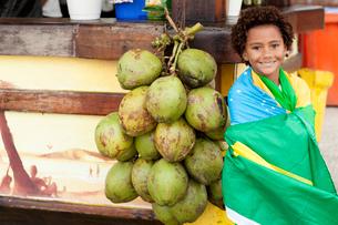 Portrait of boy wrapped in Brazilian flag next to bunch of coconuts on Ipanema beach, Rio De Janeiroの写真素材 [FYI03520063]