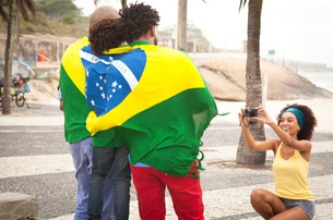 Young mother photographing family wrapped in Brazilian flag on Ipanema beach, Rio De Janeiro, Brazilの写真素材 [FYI03520064]