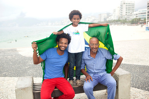 Mid adult man with father and son holding up Brazilian flag on park bench, Ipanema beach, Rio De Janの写真素材 [FYI03520066]