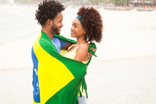 Smiling couple wrapped in Brazilian flag on Ipanema beach, Rio De Janeiro, Brazilの写真素材 [FYI03520067]