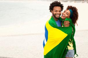 Couple hugging wrapped in Brazilian flag on Ipanema beach, Rio De Janeiro, Brazilの写真素材 [FYI03520068]