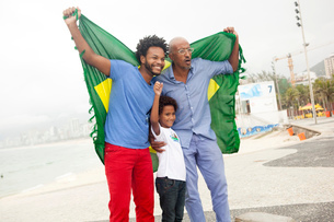 Mid adult man with father and son holding up Brazilian flag on Ipanema beach, Rio De Janeiro, Brazilの写真素材 [FYI03520069]