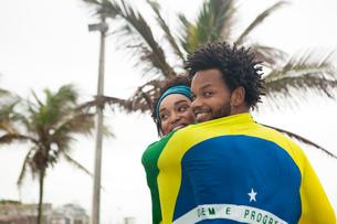 Rear view of couple wrapped in Brazilian flag on Ipanema beach, Rio De Janeiro, Brazilの写真素材 [FYI03520072]