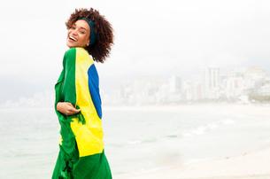 Portrait of young woman wrapped in Brazilian flag on Ipanema beach, Rio De Janeiro, Brazilの写真素材 [FYI03520074]
