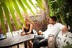 Couple enjoying drink on patioの写真素材 [FYI03520183]