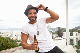 Man drinking on terrace, Sugarloaf Mountain in background, Rio, Brazilの写真素材 [FYI03520221]
