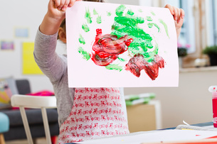 Girl holding up painting at homeの写真素材 [FYI03520263]