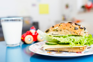 Sandwich, glass of milk, toy car on tableの写真素材 [FYI03520302]