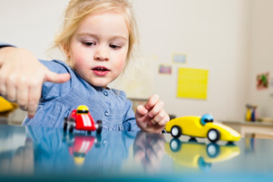 Girl playing with toy cars at homeの写真素材 [FYI03520303]