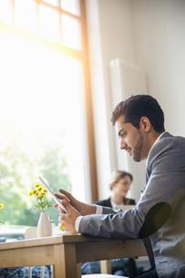Man using digital tablet in cafeの写真素材 [FYI03520454]