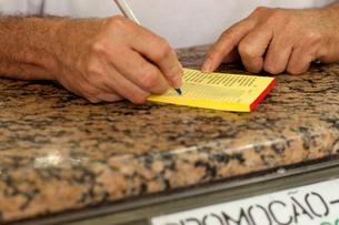 Close up of male hands writing order in juice bar, Copacabana town, Rio De Janeiro, Brazilの写真素材 [FYI03520524]