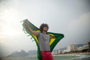 Smiling young man holding up Brazilian flag on Ipanema beach, Rio De Janeiro, Brazilの写真素材 [FYI03520563]