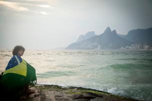 Young man wrapped in Brazilian flag sitting on rock, Ipanema beach, Rio De Janeiro, Brazilの写真素材 [FYI03520567]