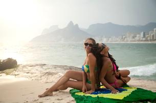 Portrait of two young women sitting on Brazilian flag,  Ipanema beach, Rio De Janeiro, Brazilの写真素材 [FYI03520579]