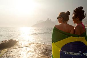 Rear view of  two young women wrapped in Brazilian flag, Ipanema beach, Rio De Janeiro, Brazilの写真素材 [FYI03520585]