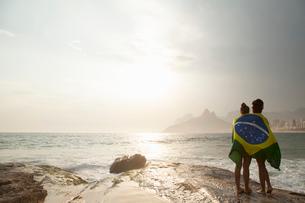 Rear view of  two young women wrapped in Brazilian flag on Ipanema beach, Rio De Janeiro, Brazilの写真素材 [FYI03520586]