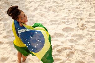 Overhead portrait of young woman wrapped in Brazilian flag, Ipanema beach, Rio De Janeiro, Brazilの写真素材 [FYI03520589]