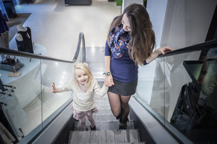 Mother and young daughter moving up escalator in shopping mallの写真素材 [FYI03520618]
