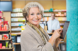 Portrait of senior woman using digital tablet to check medicine online in pharmacyの写真素材 [FYI03520695]