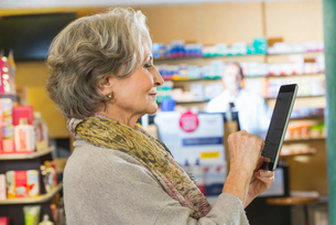 Senior woman using digital tablet to check medicine online in pharmacyの写真素材 [FYI03520698]