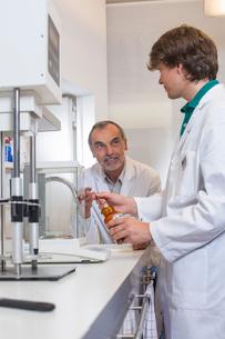 Pharmacist and trainee mixing medicine in pharmacyの写真素材 [FYI03520699]