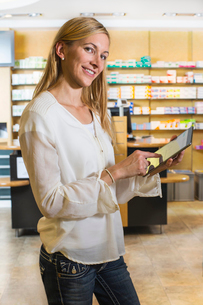 Portrait of woman using digital tablet to check medicine online in pharmacyの写真素材 [FYI03520701]