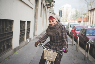 Portrait of young woman riding bicycle, wearing winter clothesの写真素材 [FYI03520817]